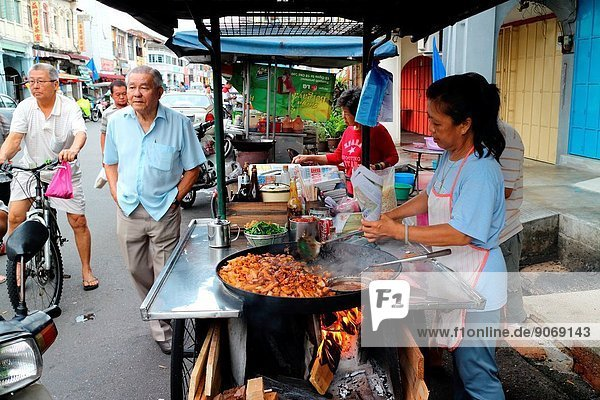 cooking stir fried cha kueh in a wok in Penang  Malaysia