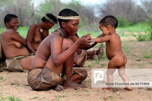 San mother with her kid excercising the first steps  Namibia  Africa.