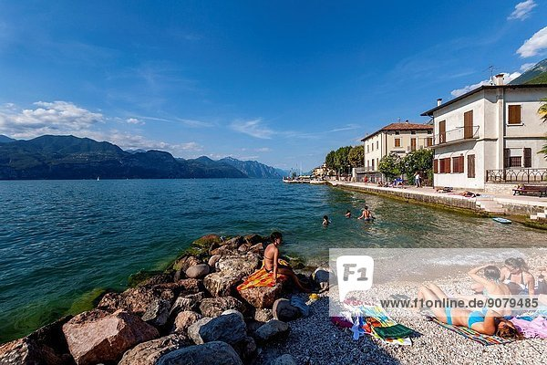 Women Sunbathing On A Beach  Lake Garda  Veneto  Italy.