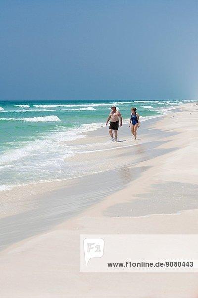Couple walking along Gulf of Mexico waterline on Santa Rosa Island in Gulf Breeze  Florida