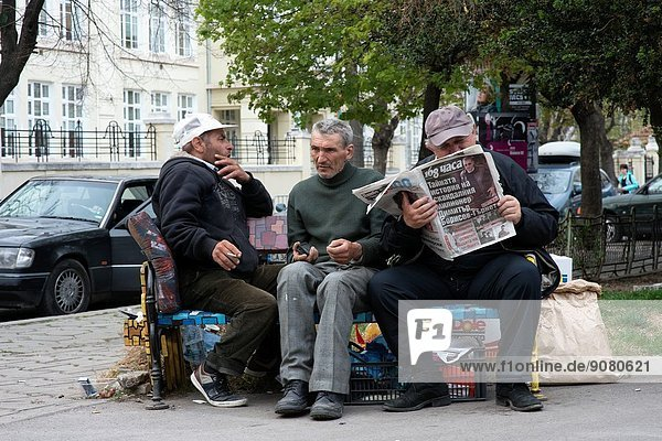 6 September Street  Sofia  Bulgaria. Three old men sitting on a park bench  reading a newspaper  smoking a cigarette and holding a mobile phone  while enjoying each others company.