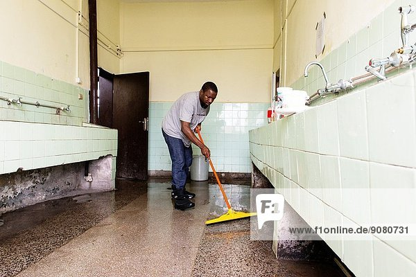 Harmanli  Bulgaria. African refugee cleaning the bathroom in one of the many refugee centre's residential buildings.