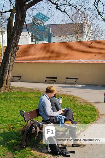 Young couple in their 20s both reading ebooks  Kampa island  Mala strana  Prague  Czech Republic  Europe.