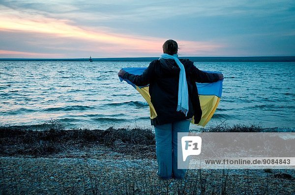 Pro-Ukrainian woman with a national flag stands on a shore of Donuslav Lake to support marines from U311 Cherkasy minesweeper.