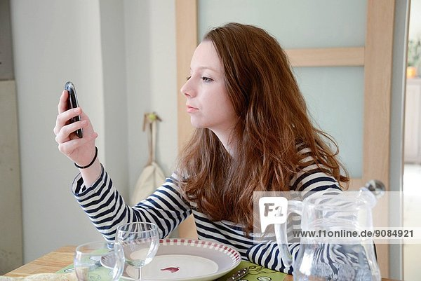 Teen age girl sending or reading a text message to another mobile.