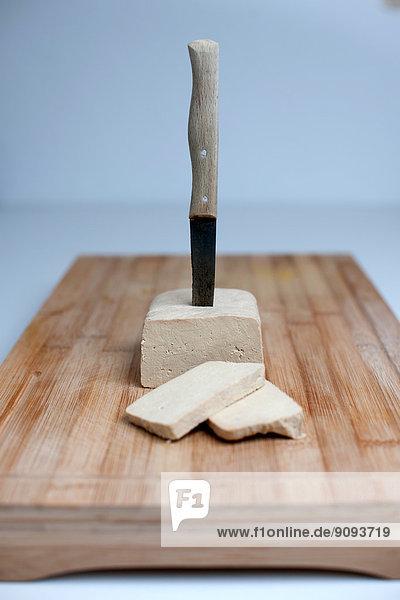 Ein Messer steckt in einem Block Tofu.