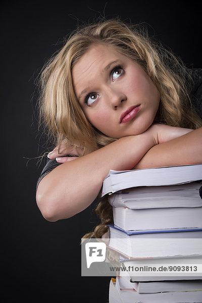 Porträt einer jungen Frau  die sich auf einen Stapel Bücher stützt.