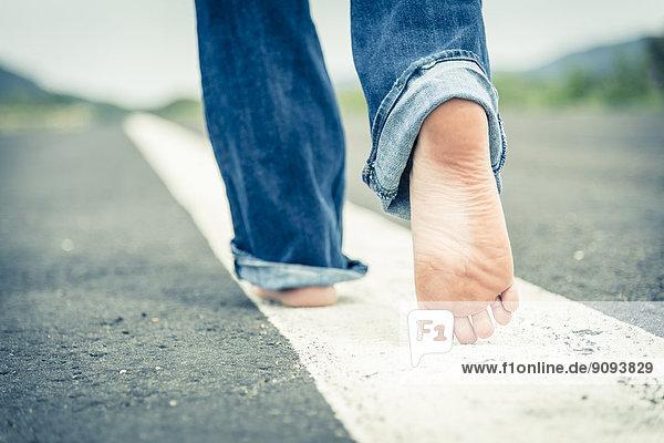 Junge Frau geht barfuß auf der Mittellinie der leeren Straße  Teilansicht