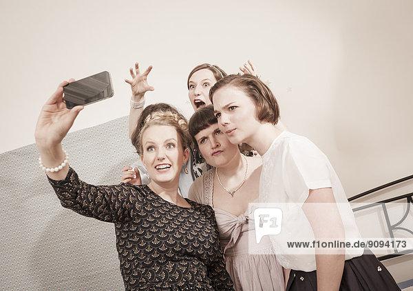 Junge Frauen in Vintage-Kleidern mit einem Selfie