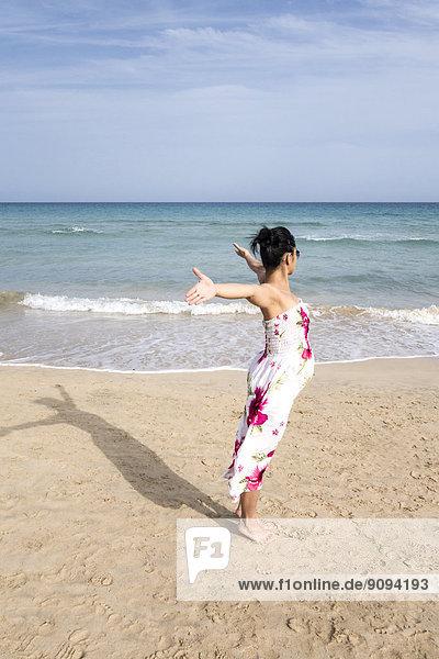Spanien  Fuerteventura  Schwangere mit ausgestreckten Armen am Strand