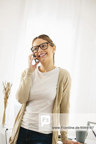 Porträt der Frau beim Telefonieren mit dem Smartphone im modernen Home Office