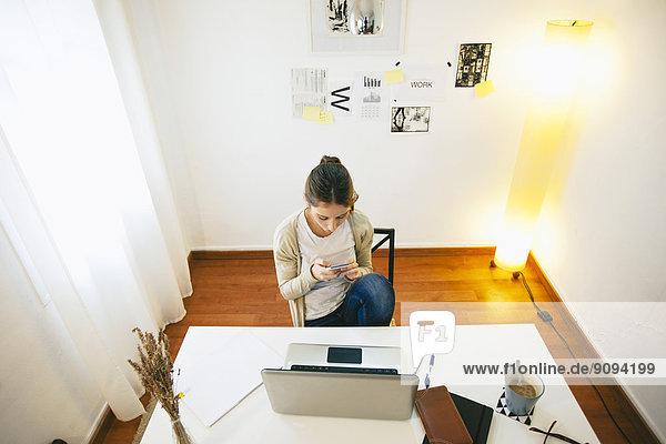 Frau mit Smartphone im modernen Home-Office  erhöhte Ansicht