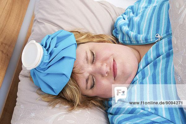 Deutschland  Mittlere erwachsene Frau im Bett liegend mit Eisbeutel
