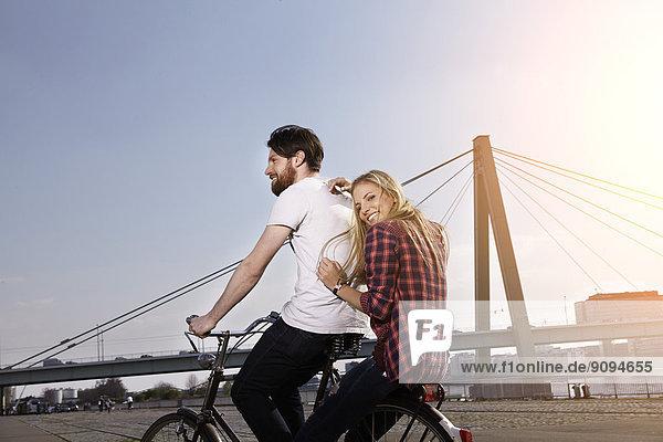Glückliches Paar beim Fahrradfahren am Flussufer