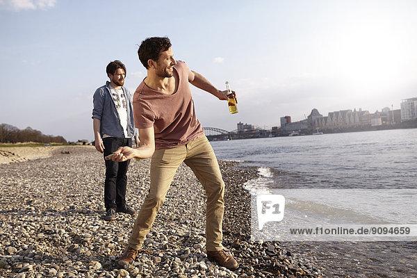 Zwei Freunde überspringen Steine am Fluss