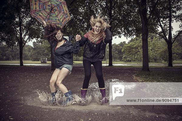 Zwei verspielte junge Frauen mit Schirmspringen in Pfütze