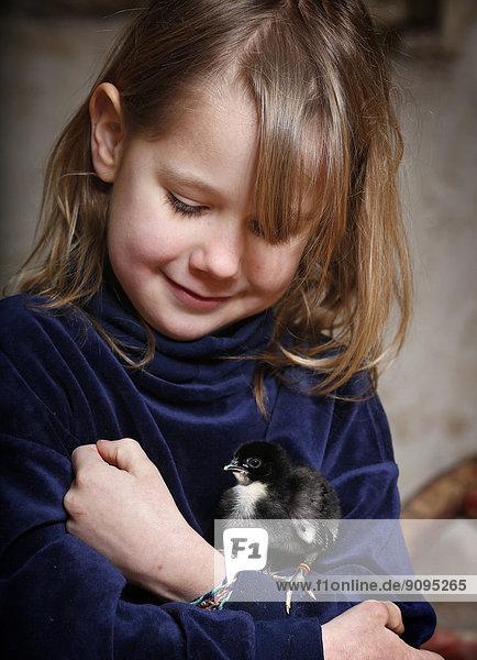 Porträt eines kleinen Mädchens mit einem Hühnerbaby