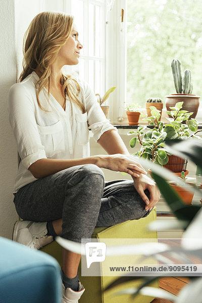 Junge Frau  die zu Hause zwischen ihren Pflanzen sitzt und aus dem Fenster schaut.
