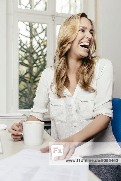 Lachende blonde junge Frau am Schreibtisch