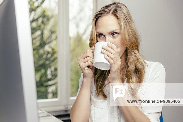 Blonde junge Frau am Schreibtisch  die eine Tasse Kaffee trinkt.