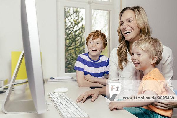 Glückliche Mutter mit zwei Söhnen auf dem Computerbildschirm