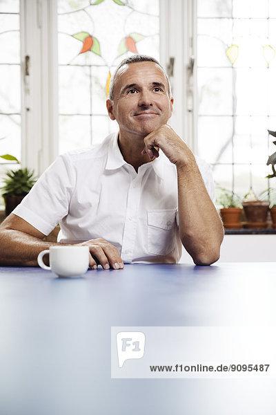 Porträt eines lächelnden Mannes mit einer Tasse Kaffee am blauen Tisch