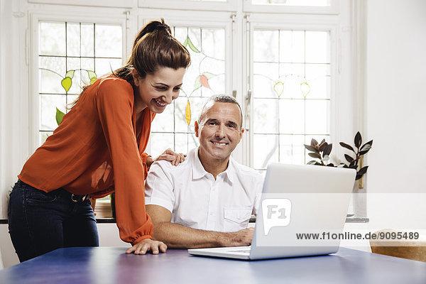 Erwachsener Mann und junge Frau mit Laptop zu Hause