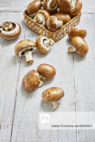 Korb mit Crimini-Pilzen auf grauem Holztisch
