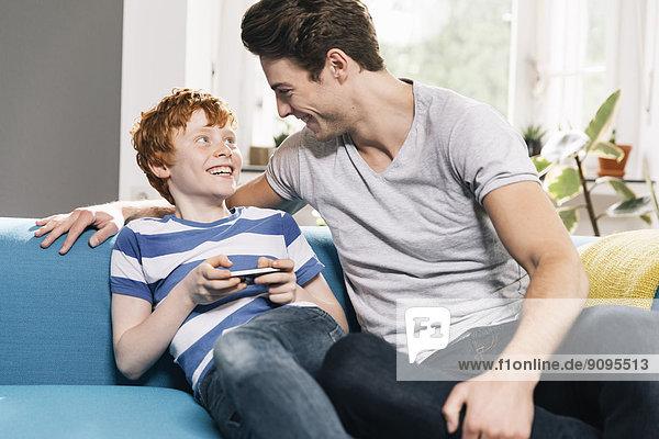 Vater und Sohn sitzen auf der Couch und schauen sich an.