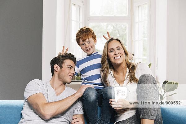 Porträt einer jungen Familie  die auf der Couch im Wohnzimmer sitzt.