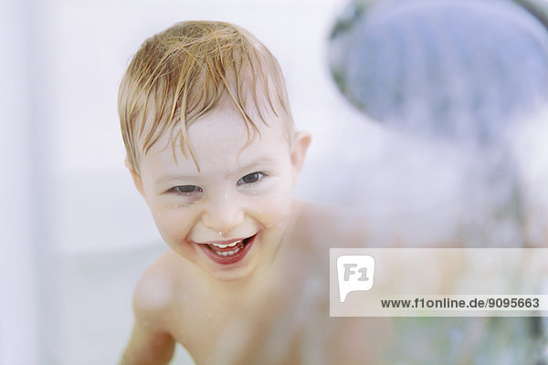 Porträt eines kleinen Jungen mit Duschkopf