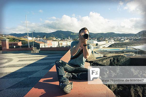 Portugal  Azoren  Sao Miguel  Mann an der Wand beim Fotografieren
