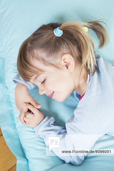 Porträt eines kleinen Mädchens  das auf einem Bohnensack schläft  erhöhte Ansicht Porträt eines kleinen Mädchens, das auf einem Bohnensack schläft, erhöhte Ansicht