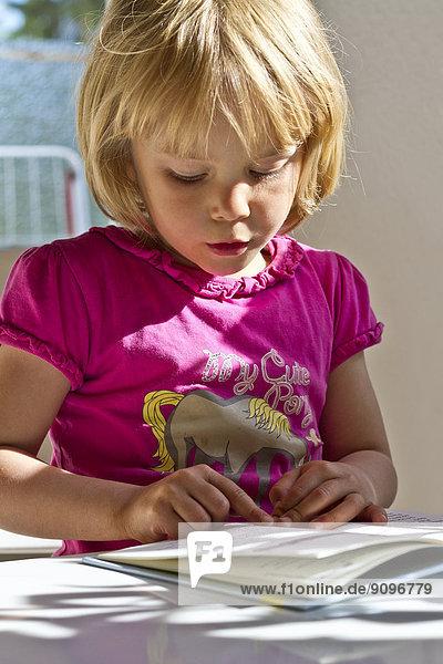 Mädchen liest in einem Buch Mädchen liest in einem Buch