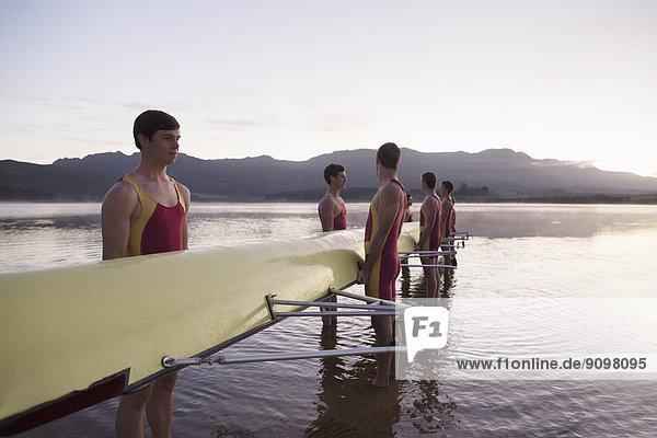 Ruderteam mit Schädel im See bei Tagesanbruch Ruderteam mit Schädel im See bei Tagesanbruch