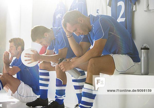 Disappointed soccer players sitting in locker room