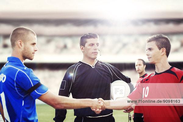 Fußballspieler beim Händeschütteln auf dem Spielfeld