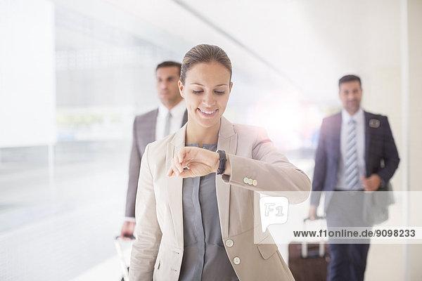 Geschäftsfrau überprüft Armbanduhr im Flur