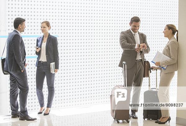 Geschäftsleute mit Koffern sprechen im Flur