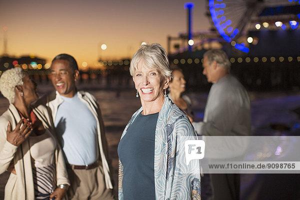 Porträt einer begeisterten Seniorin mit Freunden am Strand bei Nacht