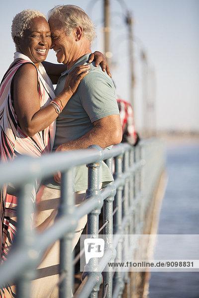Seniorenpaar beim Umarmen am Pier