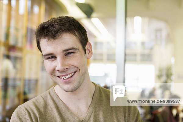 Portrait of handsome young businessman smiling in office