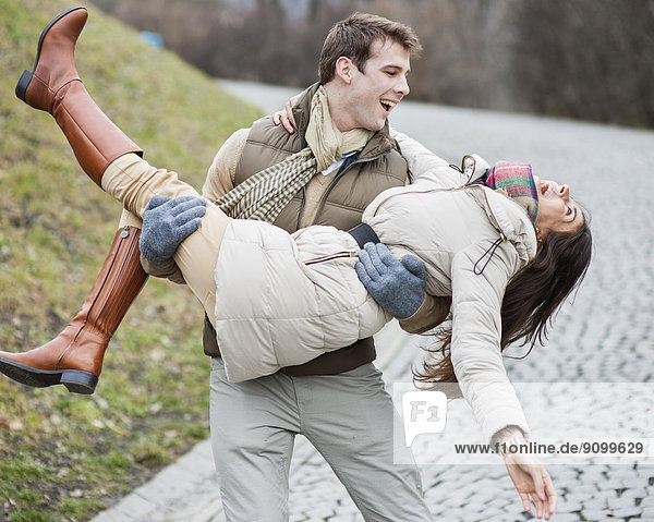 Happy man carrying woman in park
