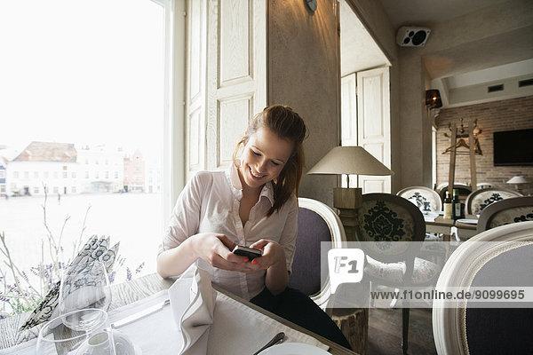 Geschäftsfrau  lächeln  Telefon  Text  Restaurant  Kurznachricht  jung  Tisch  Handy