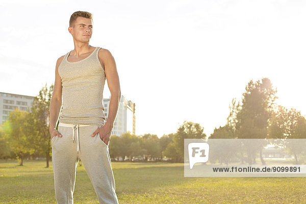 Confident jogger standing in park