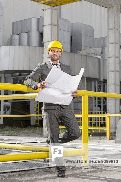 Außenaufnahme  Portrait  Industrie  Architekt  Blaupause  jung  Länge  voll