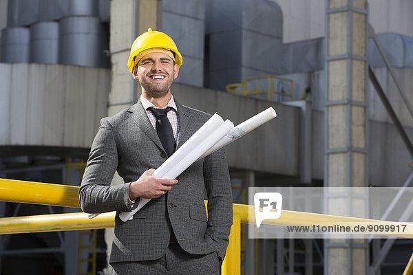 Außenaufnahme  Portrait  lächeln  Gebäude  halten  Architekt  Blaupause  jung