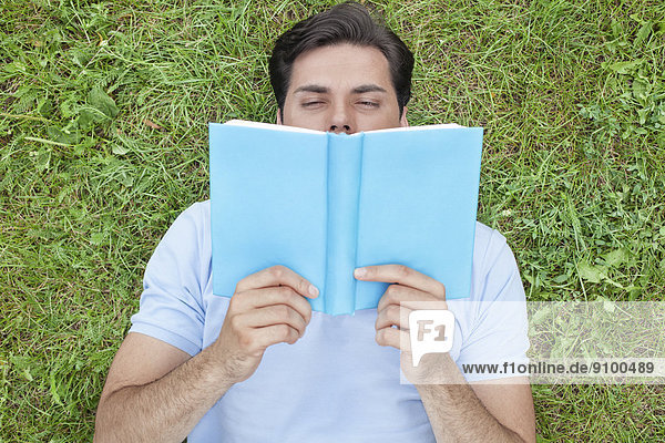 liegend  liegen  liegt  liegendes  liegender  liegende  daliegen  Mann  Buch  jung  Gras  Taschenbuch  vorlesen