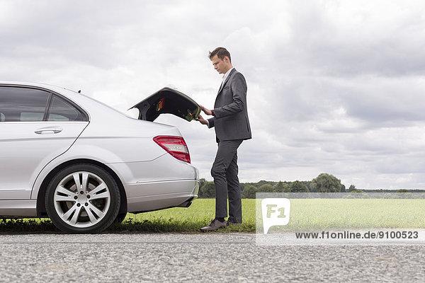 aufmachen  Geschäftsmann  Ländliches Motiv  ländliche Motive  Auto  Kofferraum  Ansicht  jung  Länge  Seitenansicht  zerbrochen  voll