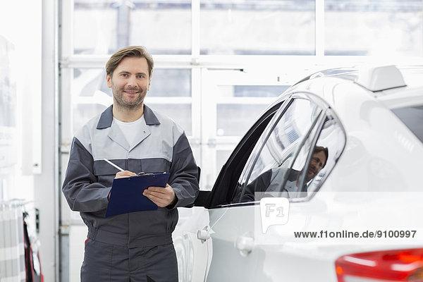 stehend  Portrait  Klemmbrett  lächeln  Auto  halten  reparieren  Laden  Mechaniker